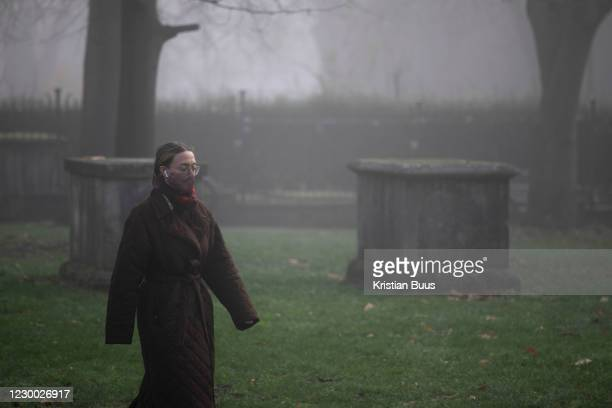 Woman wearing a face mask and ear plugs makes her way past a grave yard on a misty morning on 27th of November 2020, in Hackney, London, United...
