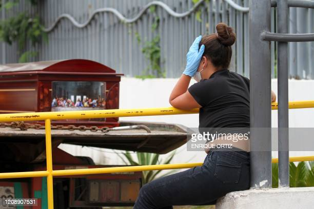A woman wearing a face mask and gloves mourns as she waits for the corpse of a relative outside a hospital in Guayaquil Ecuador on April 1 2020...
