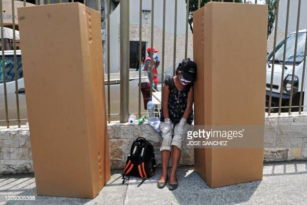 Woman wearing a face mask and gloves mourns next to cardboard boxes used coffins outside a cemetery in Guayaquyil, Ecuador, on April 6, 2020. -...