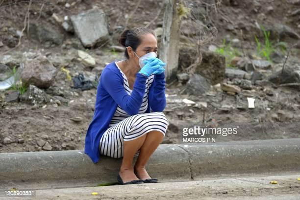 A woman wearing a face mask and gloves uses waits next waits outside a cemetery in Guayaquil Ecuador on April 1 2020 Residents of Guayaquil in...