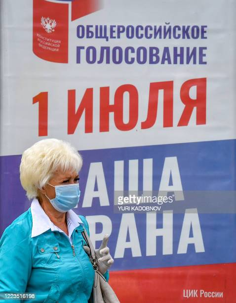 Woman wearing a face mask and gloves walks in front of a poster informing of a national vote on constitutional changes in Moscow on June 30, 2020. -...