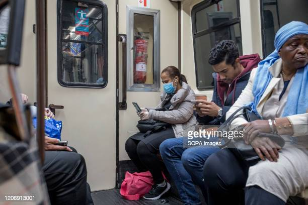 Woman wearing a face mask and plastic gloves as a protective measure against the corona virus travels in a Metro. Infections of coronavirus brought...