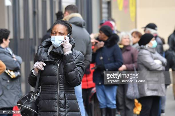Woman wearing a face mask and protectives gloves making a phone call is seen while the city imposes emergency measures to combat the Coronavirus...
