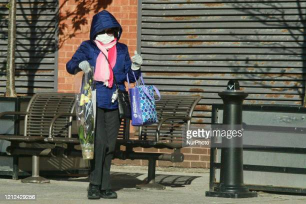 Woman wearing a face mask and surgical gloves to protect her from the novel coronavirus as she holds an orchid plant while walking in Toronto Ontario...