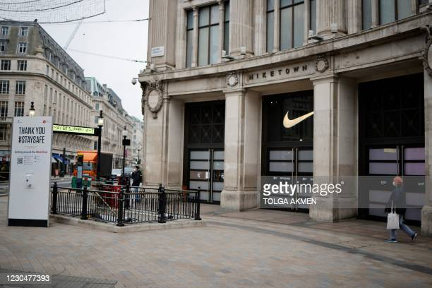 Woman wearing a face mask approaches a Stay Safe sign on Oxford Street in central London on January 8 as England entered a third lockdown due to the...