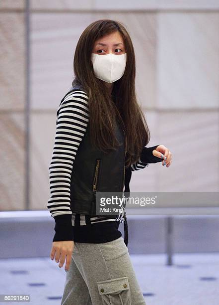 A woman wearing a face mask arrives at Sydney International Airport on April 30 2009 in Sydney Australia The World Health Organisation has issued a...