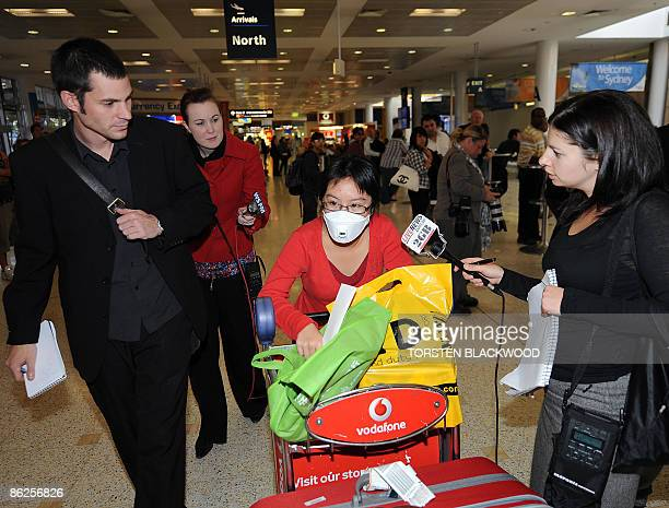 A woman wearing a face mask as a precaution against the deadly swine flu is surrounded by Australian media as she arrives at Sydney International...