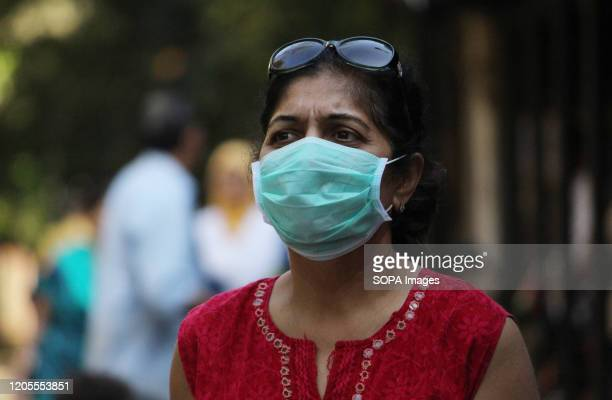 A woman wearing a face mask as a precaution against the outbreak of Coronavirus walks at the Kasturba hospital A special isolation ward has been...