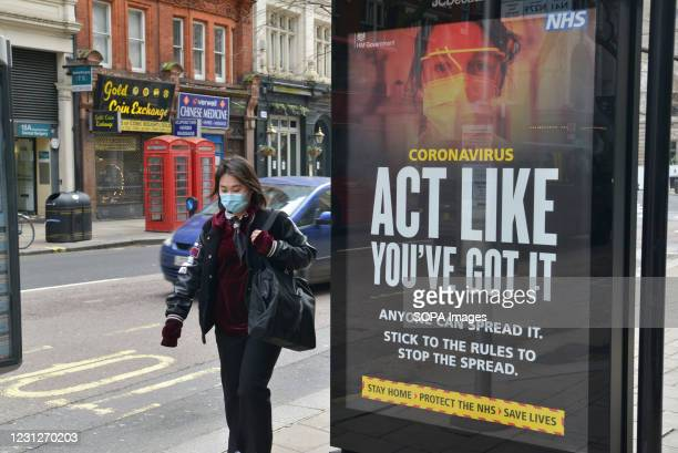 Woman wearing a face mask as a precaution against the spread of covid-19 walking past a covid-19 NHS warning sign saying 'Act Like You've Got It' at...