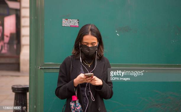 Woman wearing a face mask as a precaution against the spread of covid 19 standing next to a green background while using a mobile phone in...