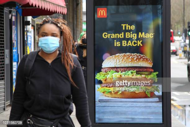 Woman wearing a face mask as a precaution against the spread of covid-19 walks past McDonald's digital advert in London.