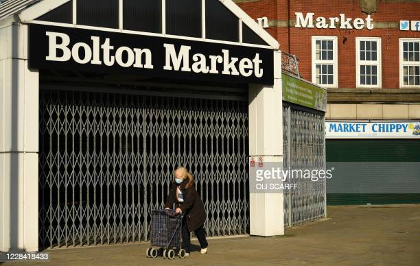 A woman wearing a face mask as a precaution against the transmission of COVID19 walks past the closed market in the centre of Bolton northern England...