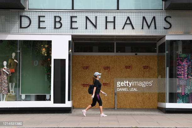 Woman wearing a face mask as a precaution walks past the shut and boarded up Debenhams department store on Oxford Street in London's main high street...
