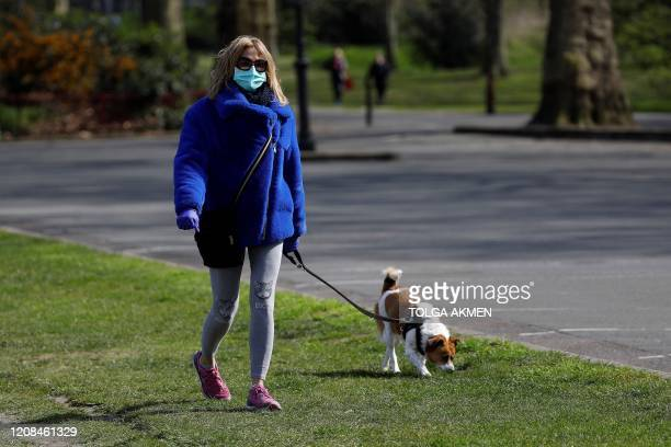 A woman wearing a face mask as a precautionary measure against Covi19=m= walks a dog to get her exercise in Battersea Park in London on March 28 as...