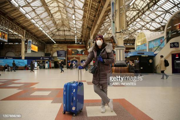 Woman wearing a face mask as a precautionary measure against covid-19, stands with her suitcase on the concourse at Victoria train Station in central...