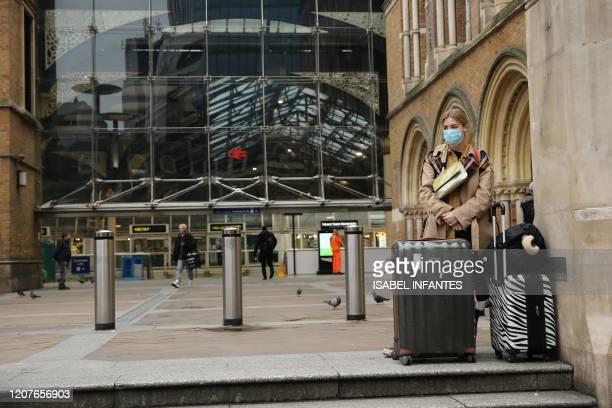 Woman wearing a face mask as a precautionary measure against covid-19, stands with her suitcases outside of Liverpool Street train Station in central...