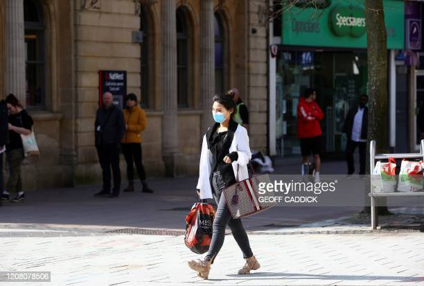 Woman, wearing a face mask as a precautionary measure against covid-19, as people stand at a distance and queue to enter a bank in Cardiff, south...