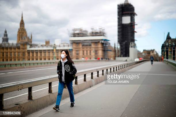 A woman wearing a face mask as a precautionary measure against COVID19 walks across Westminster Bridge in London on April 2 as life in Britain...
