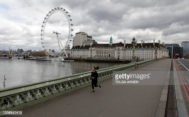 A woman wearing a face mask as a precautionary measure against COVID19 jogs across Westminster Bridge to take their daily exercise allowance in...