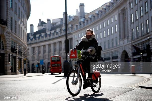 A woman wearing a face mask as a precautionary measure against COVID19 cycles past closeddown shops on an empty Regent Street in London on April 2 as...