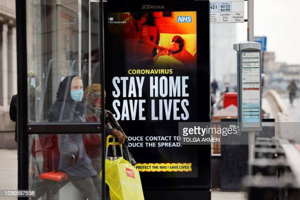 Woman wearing a face mask as a precautionary measure against COVID-19, waits in a busstop with NHS signage on keeping safe, at London Bridge in...