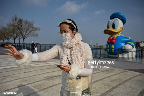 A woman wearing a face mask as a preventive measure against the COVID19 coronavirus calls her son while visiting Disneytown in Shanghai on March 10...