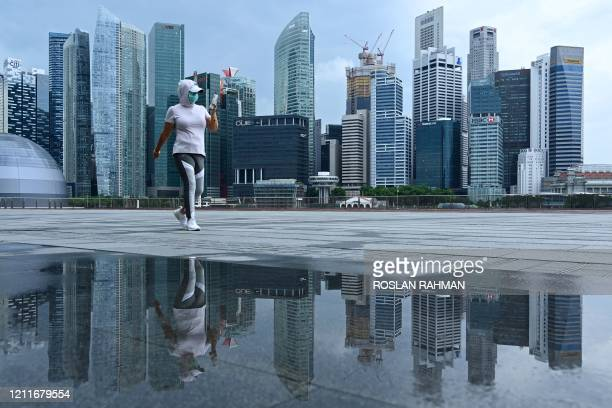 Woman, wearing a face mask as a preventive measure against the spread of the COVID-19 novel coronavirus, walks along the promenade at Marina Bay in...