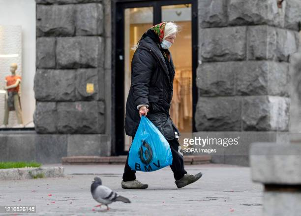 A woman wearing a face mask as a preventive measure against the spread of coronavirus is seen walking in downtown Kiev Ukraine's government plans to...