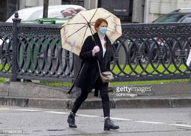A woman wearing a face mask as a preventive measure against the spread of COVID19 coronavirus holds an an umbrella to protect her from rain in...