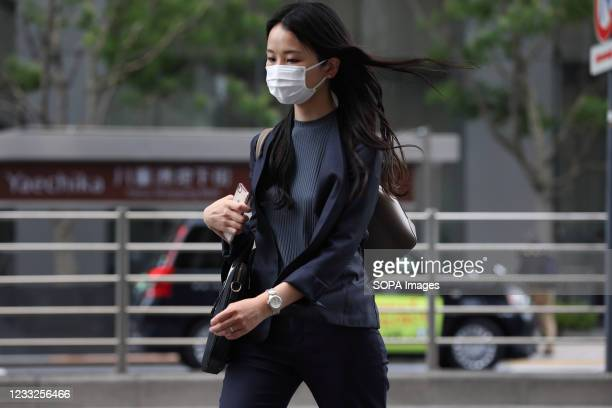 Woman wearing a face mask as a preventive measure against the spread of covid-19 walks down the street near Tokyo Station. The State of Emergency in...