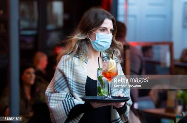 Woman wearing a face mask carries a tray of drinks at Pitch bar on April 30, 2021 in Cardiff, Wales. Outdoor hospitality reopened on Monday in Wales...