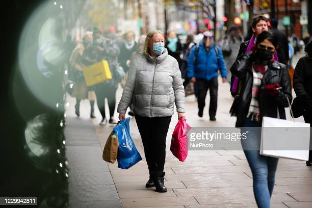 Woman wearing a face mask carries bags of shopping along Oxford Street in London, England, on December 4, 2020. London has returned to so-called Tier...