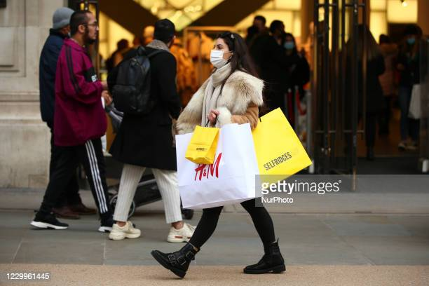 Woman wearing a face mask carries bags of shopping from clothing retailer HM and department store Selfridges along Regent Street in London, England,...