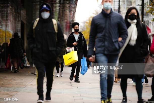 Woman wearing a face mask carries bags of shopping, including from department store Selfridges, along Oxford Street in London, England, on December...