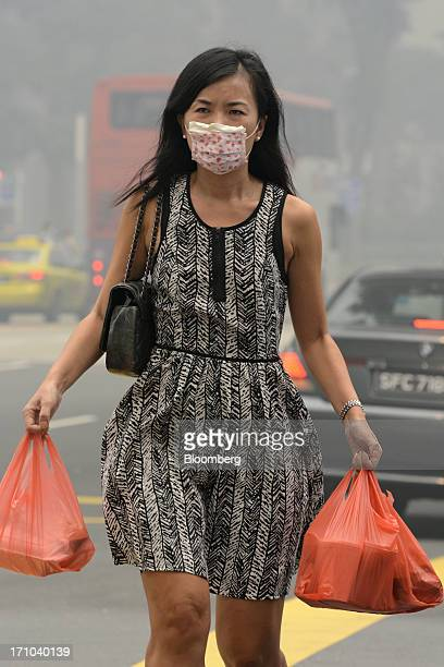 Woman wearing a face mask carries bags of takeaway food as she walks along a road during lunch hour in Singapore, on Friday, June 21, 2013....