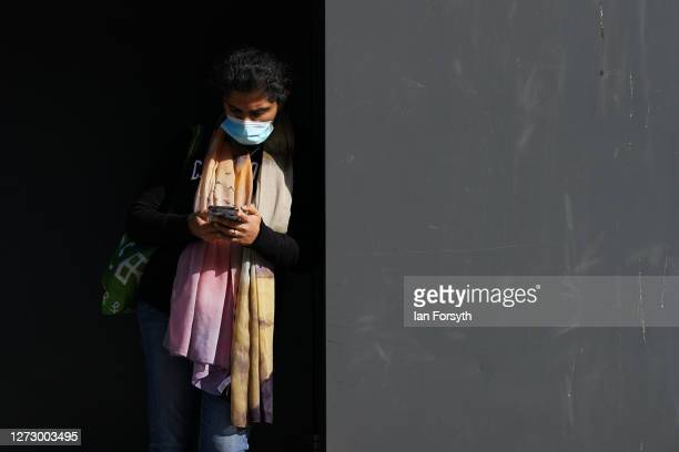 A woman wearing a face mask checks her phone in the centre of Newcastle on September 17 2020 in Newcastle upon Tyne England Almost two million people...