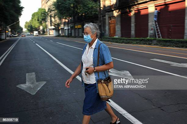 A woman wearing a face mask crosses an empty street in downtown Mexico City void of pedestrians and vehicular traffic on May 3 2009 The influenza A...