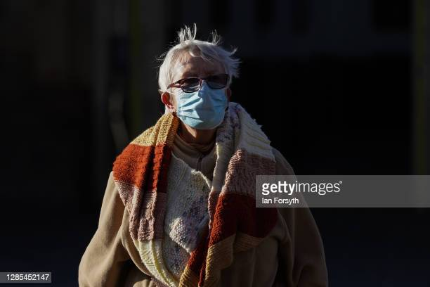 Woman wearing a face mask crosses the road outside Hull bus station on November 13, 2020 in Hull, England. Hull recorded 726.8 new cases per 100,000...