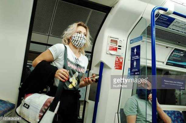 Woman wearing a face mask, currently mandated on public transport, boards a Northern line tube service at Warren Street station in London, England,...