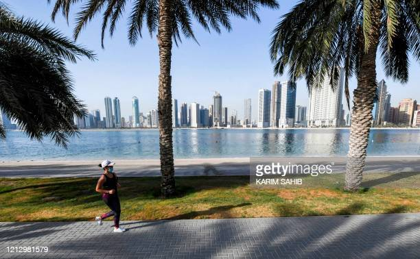 Woman wearing a face mask due to the COVID-19 coronavirus pandemic jogs along the waterfront in Sharjah as pandemic lockdown measures are eased in...