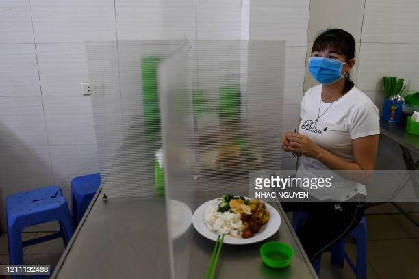 TOPSHOT A woman wearing a face mask eats lunch on a table installed with a makeshift plastic partition as a preventive measure against the spread of...