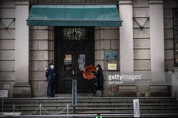 A woman wearing a face mask enters the Bank of Japan in Tokyo's financial district on March 2 2020 in Tokyo Japan Prime Minister Shinzo Abe continues...