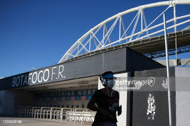 Woman wearing a face mask exercises outside the stadium prior to the match between Botafogo and Cabofriense as part of the Carioca State Championship...
