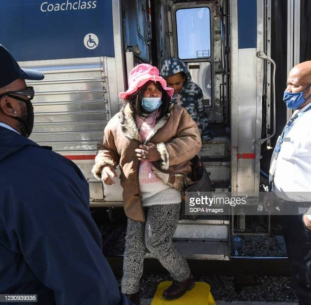 Woman wearing a face mask exits a train at the Orlando Amtrak station on the first day that the Transportation Security Administration began...