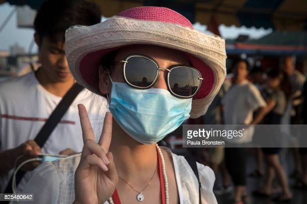 A woman wearing a face mask gives the V sign a common sight with Asians when they are posing for photos as large groups of Chinese tourists wait to...