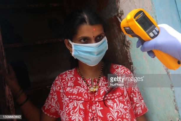 Woman wearing a face mask has her body temperature checked in the Dharavi slum area of Mumbai, India on April 14, 2020. India continues in nationwide...