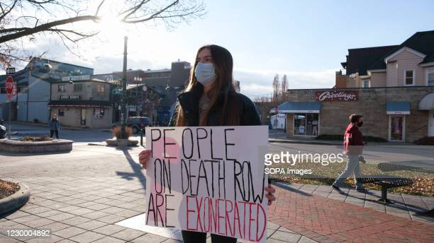 Woman wearing a face mask holds a placard in Peoples Park to protest against the death penalty, and a wave of executions at the Terre Haute federal...