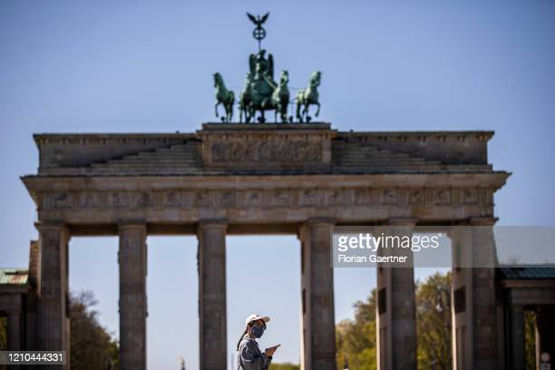 Woman wearing a face mask is pictured in front of the Brandenburg Gate on April 20, 2020 in Berlin, Germany. Some parts of Germany decided to...