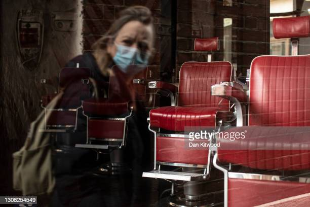 Woman wearing a face mask is reflected in the window of a closed barbers in the square mile on March 17, 2021 in London, England. Hairdressers in...