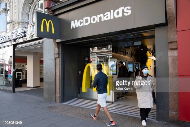 Woman wearing a face mask leaves McDonalds with her McFlurry, which is now closed as a sit down fast food restaurant, but still open for take away...